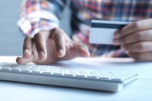 mans hand som håller ett kreditkort och använder bärbar dator för att handla online foto