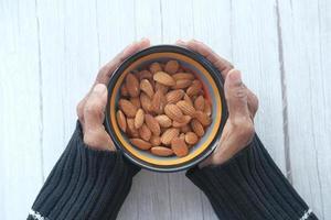 närbild av äldre kvinnahand som håller en skål på mandlar