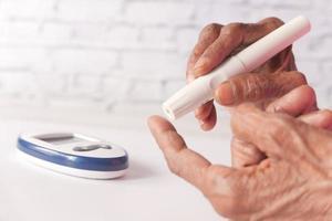 äldre kvinnas diabetiker mäter glukosnivån hemma foto