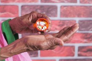 närbild av piller och kapslar i äldre kvinnas hand foto