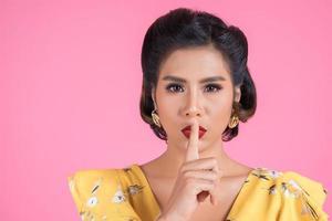 asiatisk kvinna med röda läppar och finger som visar tystnad