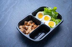 sektionerad plastmatbehållare med krutonger, sallad och skivat hårdkokt ägg