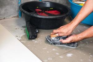händer som tvättar tennisskor bredvid hinkar fyllda med vatten och skor