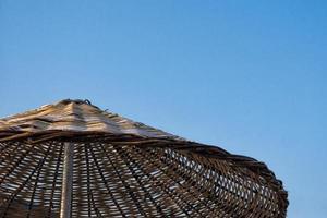 korgstrandparaply i en blå himmel foto