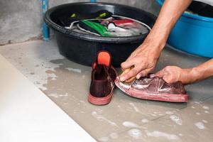 två händer som tvättar tennisskor bredvid hinkar fyllda med vatten och skor