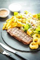grillad biff med pommes frites och färska grönsaker