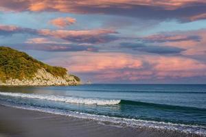 marinmålning med berg och färgglad molnig himmel foto