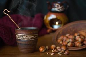 utsmyckad keramisk kopp bredvid hasselnötter på bordet foto