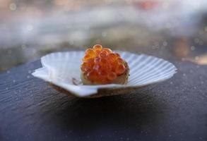 röd kaviar på en kammusselsfilé på en vit porslinsskalplatta på bordet