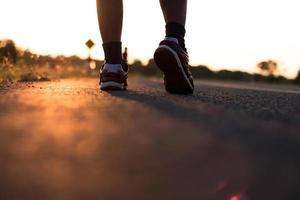 silhuett av foten som kör på en väg foto