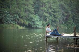 ensam man lyssnar på musik på en brygga foto
