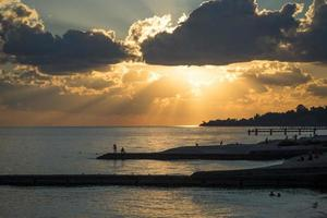 människor silhuett på en strand med solnedgång molnig himmel foto