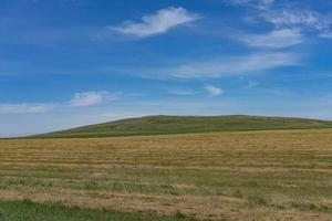 landskap med åkrar och kullar och molnig blå himmel