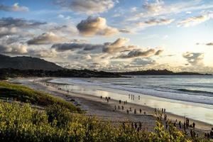 silhuett av människor vid stranden med en blå och gul solnedgång