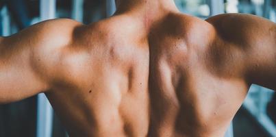 närbild av mans ryggmuskler i ett gym
