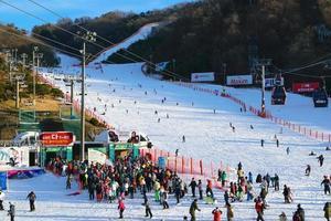människor som väntar på skidlift med människor som åker i bakgrunden på Vivaldi Park Ski World i Korea foto