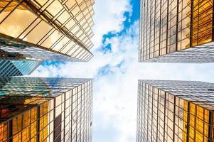 Visa tittar upp på skyskrapor med molnig blå himmel foto