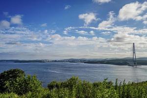 marinmålning av grönt fält vid gyllene hornvikten och zolotoy-bron med molnig blå himmel i Vladivostok, Ryssland foto