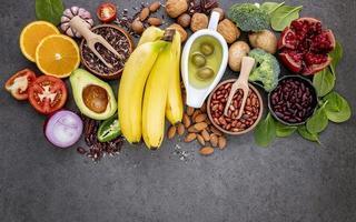 frukt, grönsaker och nötter på en grå bakgrund foto