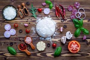 pizzaingredienser och deg på trä foto
