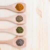 torkade kryddor i träskedar foto