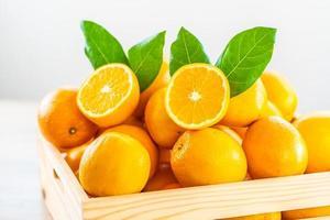 färska apelsiner i en trälåda foto