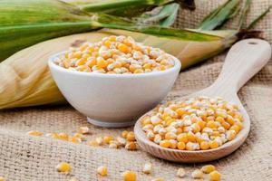 majs i en skål och på en sked foto