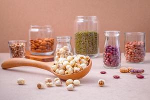 bönor och nötter i burkar och en sked foto