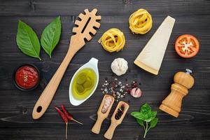 färska italienska ingredienser på mörkt trä foto