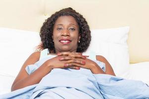 kvinna som kopplar av i sängen under täcket foto