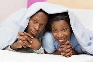ungt och vackert par i sängen foto