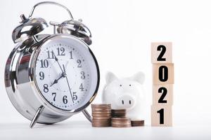 Sparande pengar spargris 2021 för nytt år med träord 2021. Pengarsparande koncept foto