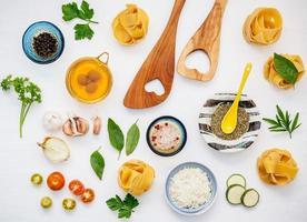 italiensk mat koncept och meny design. torkad hemlagad fettuccine med hjärtformad träspatel och ingredienser söt basilika, tomat, vitlök, persilja, lagerblad, peppar, zucchini och parmesanost platt låg. foto
