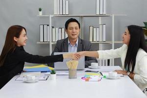 affärskvinnor som skakar hand efter att ha förhandlat om affärssamarbete