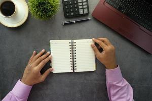 man bläddrar igenom en anteckningsbok på skrivbordet