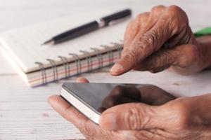 äldre kvinna som använder ett smart telefonslut upp