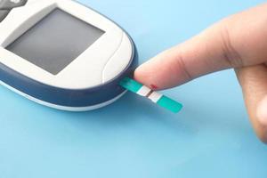mans finger som mäter glukosnivån foto