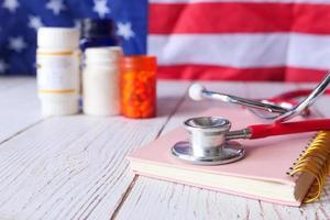 stetoskop och piller på anteckningsblocket på bordet foto