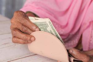 närbild på personen som sparar kontanter i plånboken