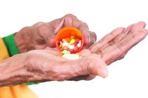 äldre kvinna som tar piller foto