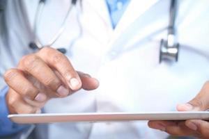 läkare i vit kappa använder en digital tablett