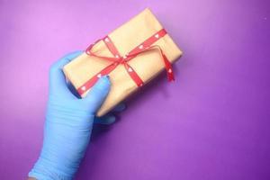 blå handskhand som levererar en gåva
