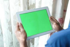 ung man som använder den digitala minnestavlan hemma med den gröna skärmen foto