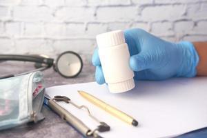läkarens hand som håller pillerbehållaren