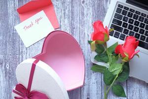 Alla hjärtans dag presentask och blomma på träbord