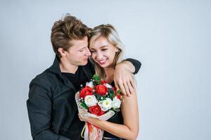 porträtt av lyckliga unga par med blommor i studio foto