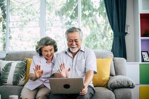 äldre par som talar och använder bärbar dator