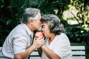 äldre par som leker och äter lite frukt foto