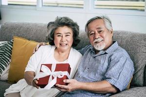 äldre par överraskar med presentask i vardagsrummet foto