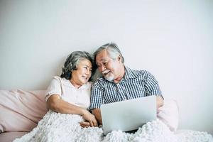 äldre par som pratar och använder bärbara datorn i sovrummet